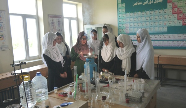 Photo from Afghnaischer Frauenverein showes women at scholl doing chemistry