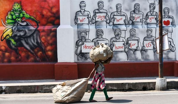 Girl in Calcutta, India walks with collected waste in front of a Corona awareness poster.